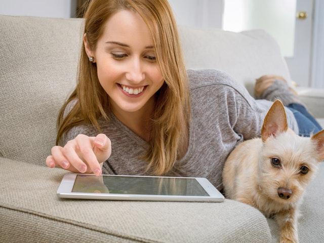 Flicka med hund och iPad